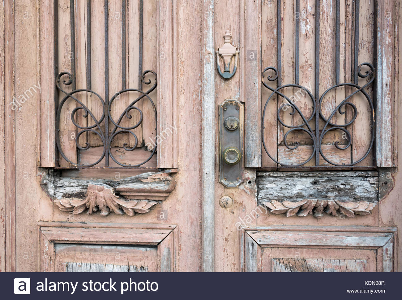 Weathered old colonial architectural detail. Timeworn wooden door with symmetrical iron grill and pattern. - Stock Image