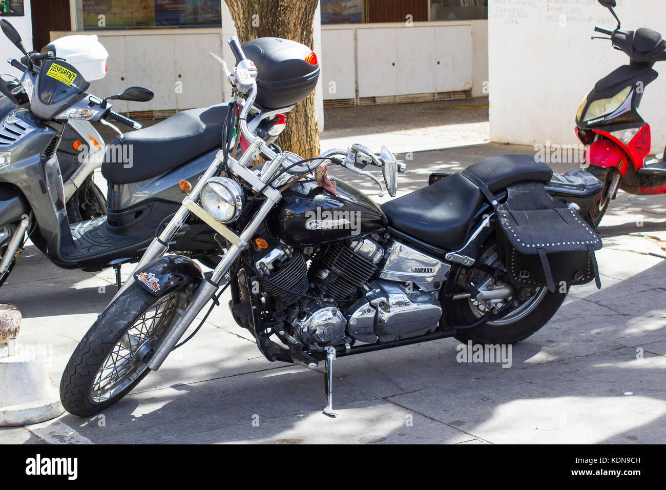 A japanese made Yamaha Dragstar motor cycle parked in a supermarket car park in Albuferia in Portugal - Stock Image