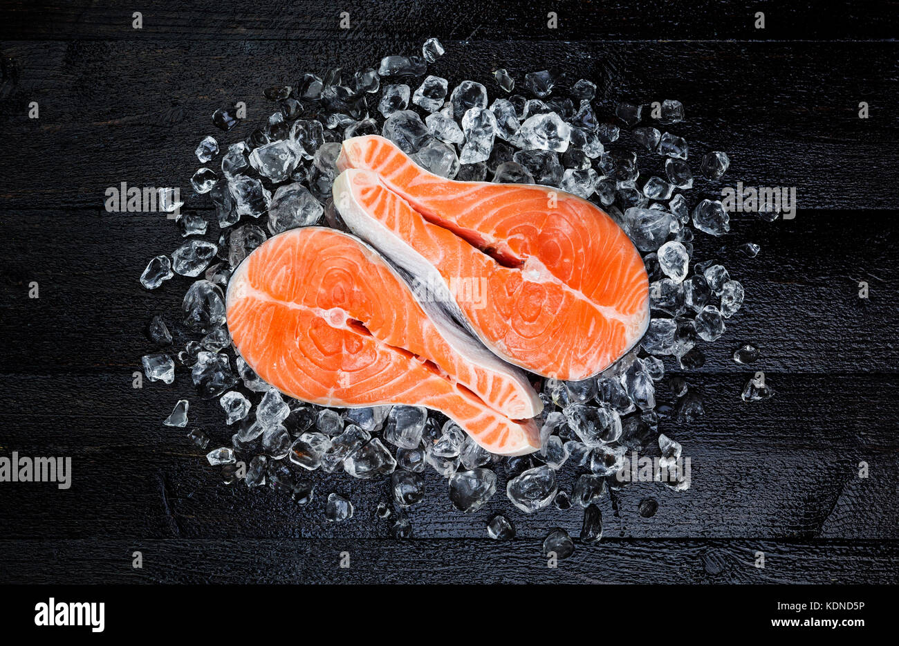 Salmon steak on ice on black wooden table top view - Stock Image
