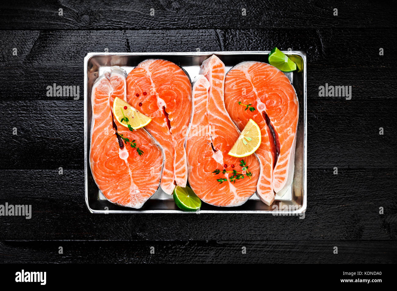 Salmon steaks on metal tray on black wooden table top view - Stock Image