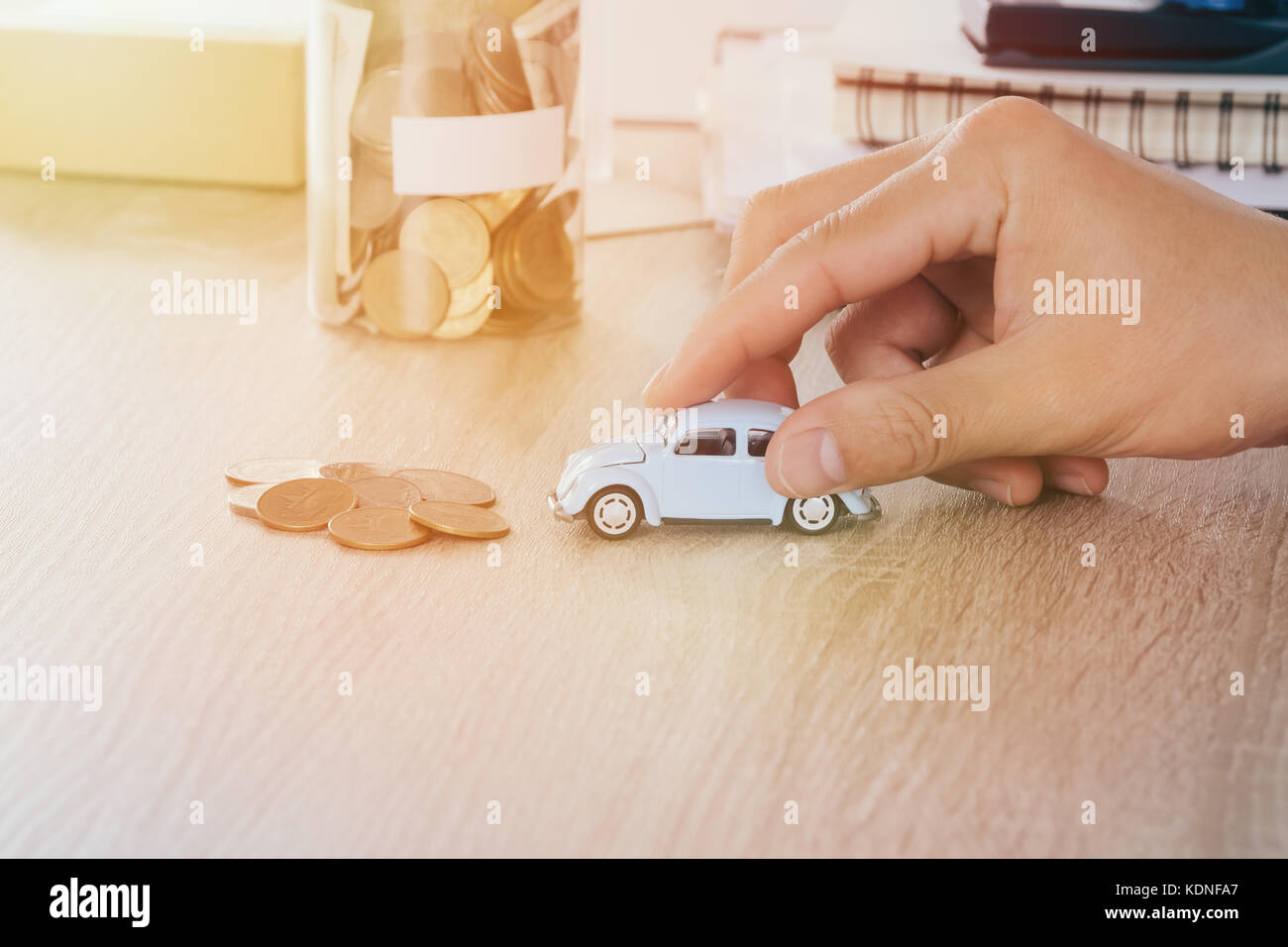 Car toy in the men hand on desk with blured money coin in jar bank saving Concept for maintenance costs and taxes - Stock Image