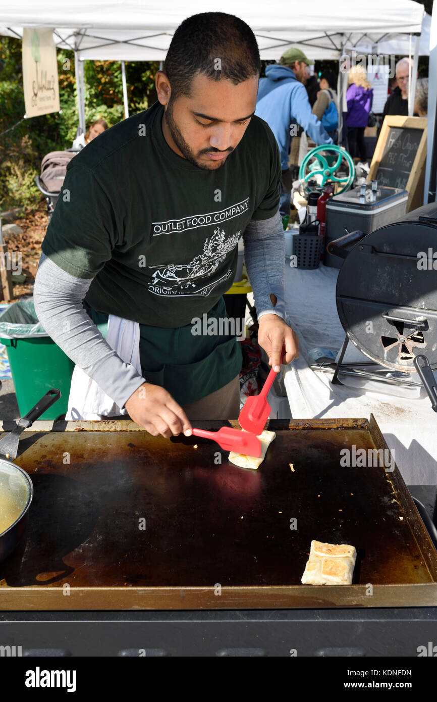 Young man carefully preparing food on a grill at the Saturday Wellington Farmers Market in Prince Edward County - Stock Image