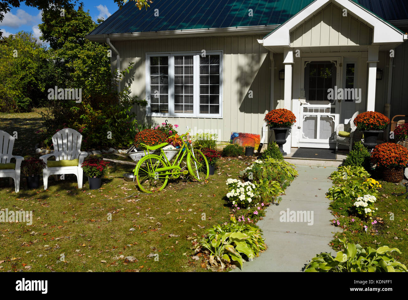 Colorful Fall front garden with green bicycle in Wellington, Prince Edward County Ontario Canada - Stock Image