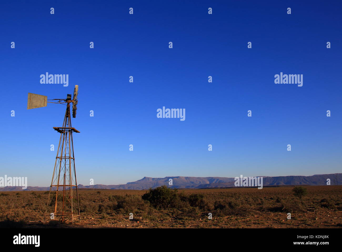 Windmill in a vast open and dry landscape with a clear blue sky in landscape format with copy space - Stock Image