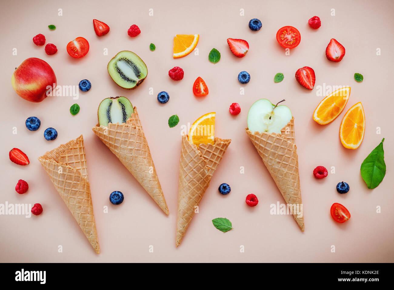 Cones and colorful various fruits raspberry ,blueberry ,strawberry ,orange slice , halve kiwi ,apple,tomato and Stock Photo