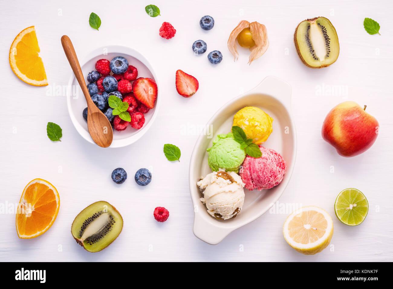 Colorful ice cream with mixed berry and various fruits raspberry ,blueberry ,strawberry ,orange slice , halve kiwi - Stock Image