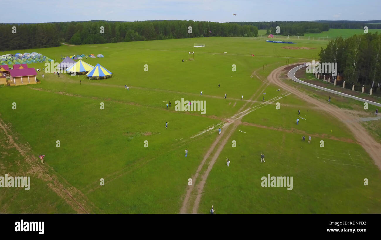People flie a kite on grass in summer day. Group children flying kite outdoor. Flying kite in motion making loops Stock Photo