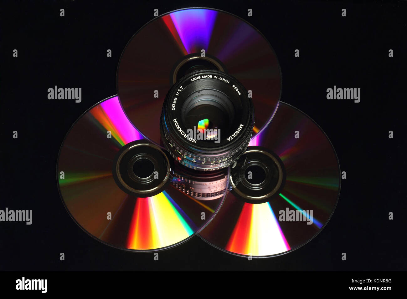 Old Minolta 50 mm lens reflected on DVD. - Stock Image