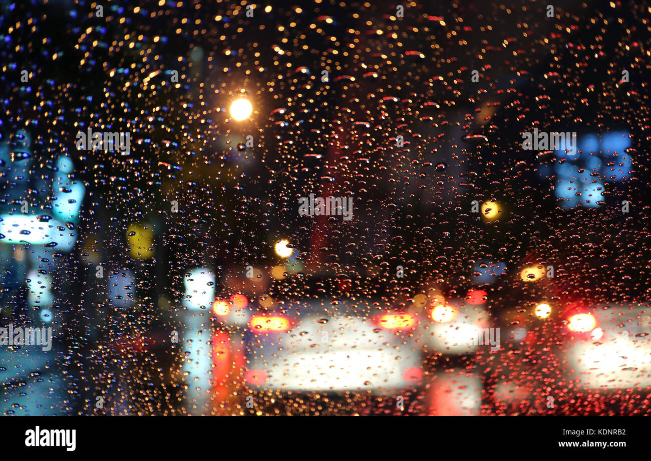 Blurred vehicles and tail lamps seen through the raindrops on car windshield at night - Stock Image