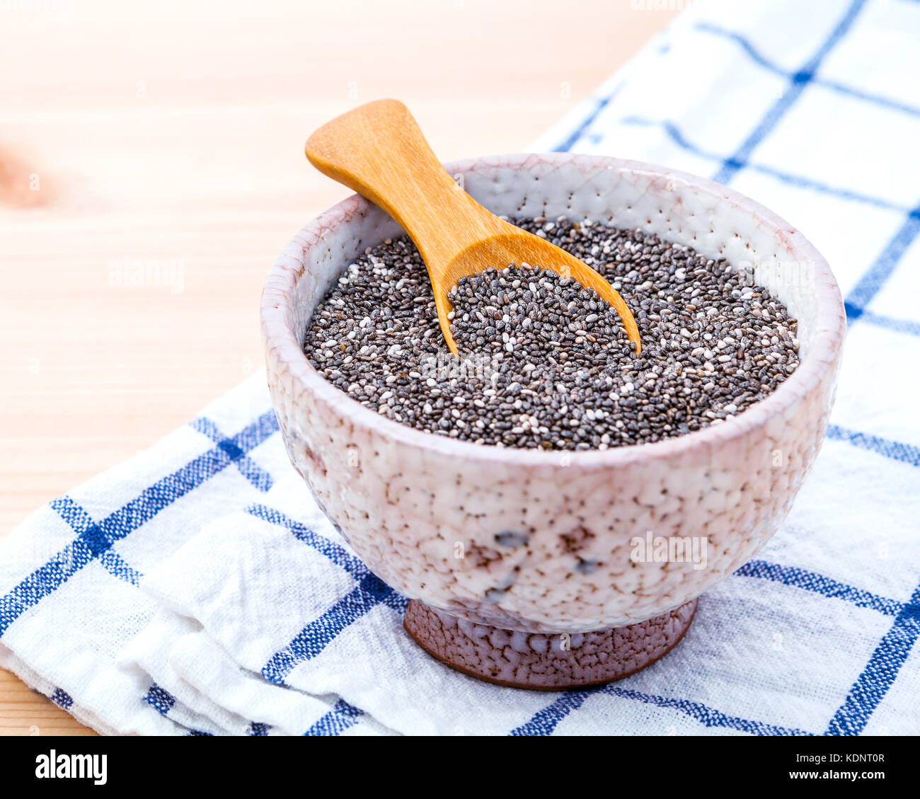 Nutritious chia seeds in ceramic bowl on wooden table for diet foods ingredients . Nutritious Foods and Super foods - Stock Image