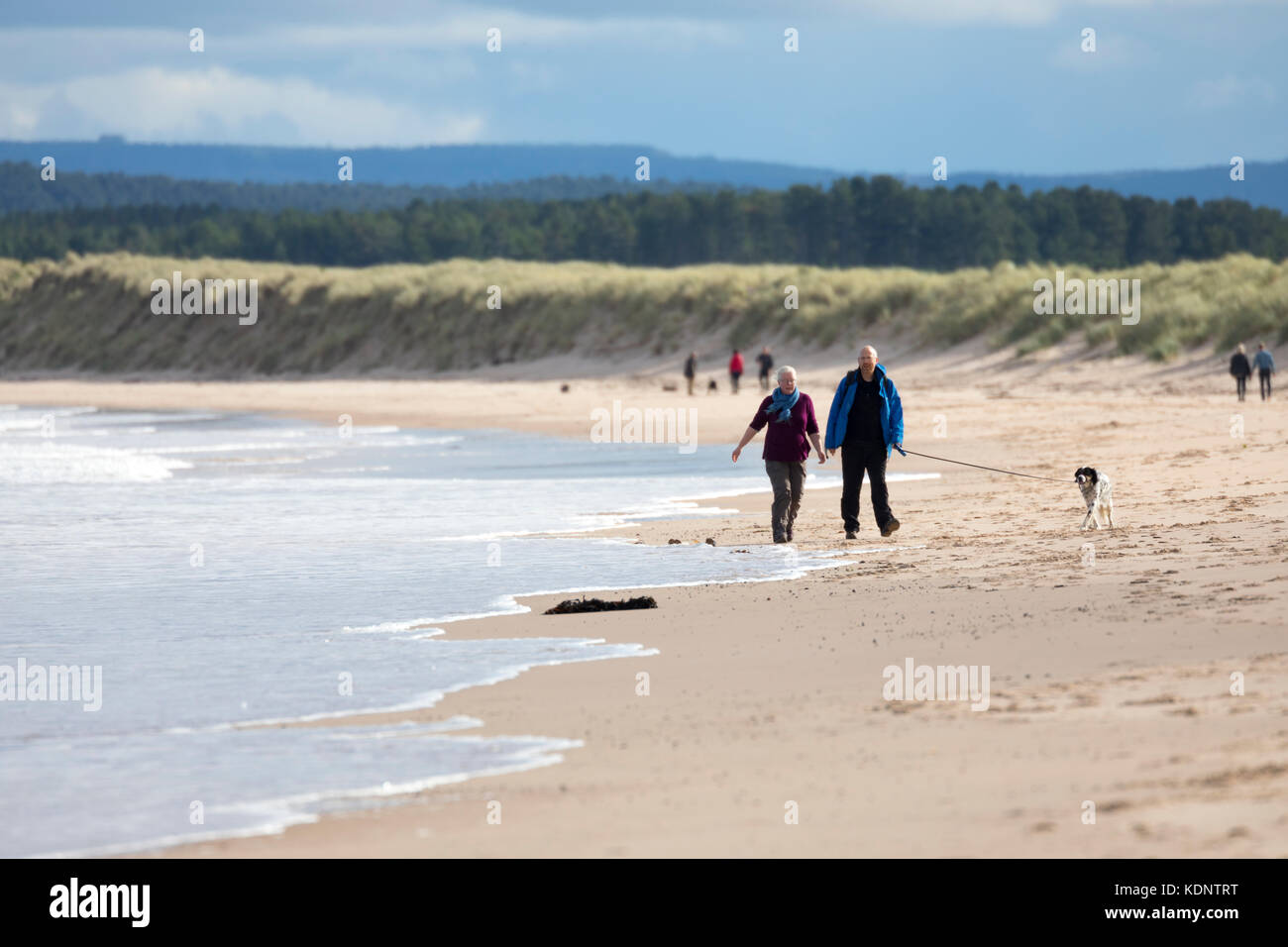Walkers enjoying autumn sunshine on the sandy beach on the picturesque seaside resort town of Lossiemouth, Scotland - Stock Image