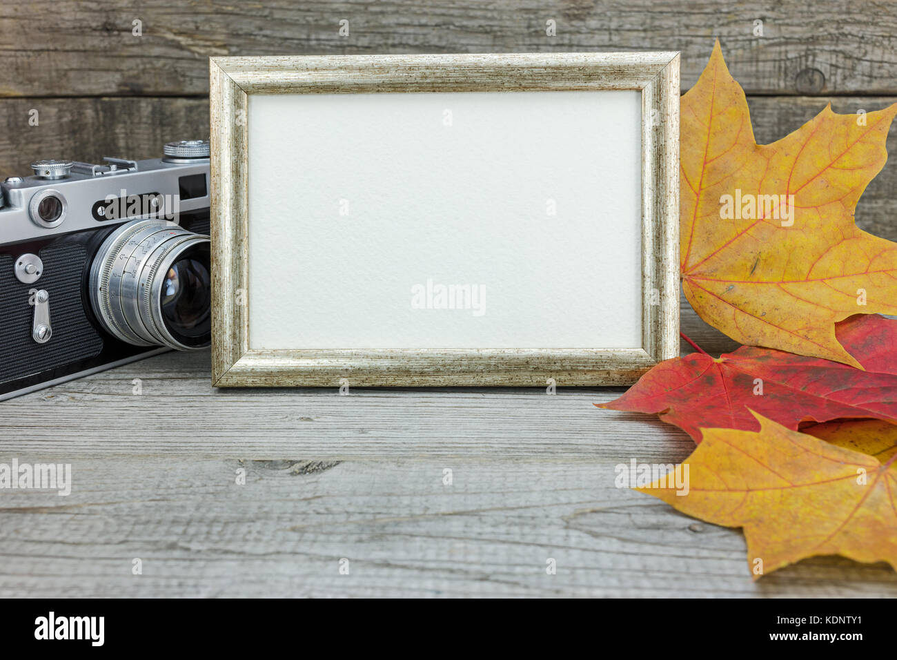 retro camera and photo frame on wooden background with colorful ...