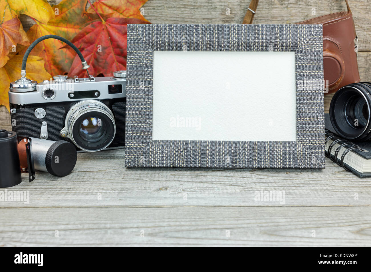 grunge wooden background with classic camera, empty photo frame, lens and film rolls Stock Photo