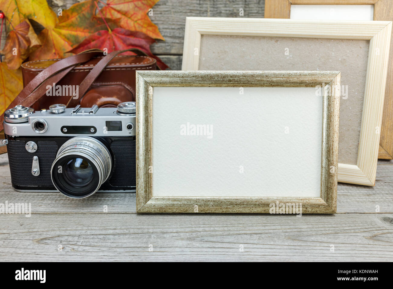 empty photo frames and classic camera on gray wooden table with ...
