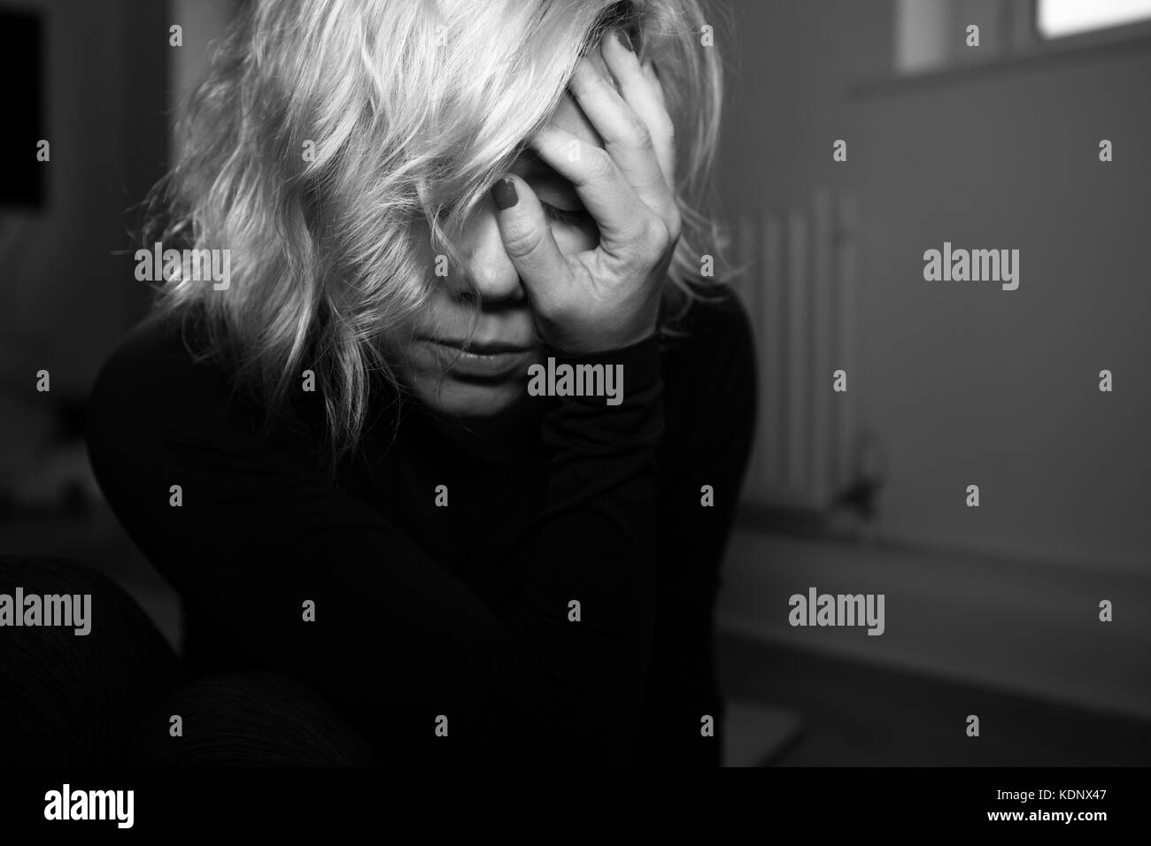 Woman holds her head in her hand.  Blonde woman in despair depressed tired. - Stock Image