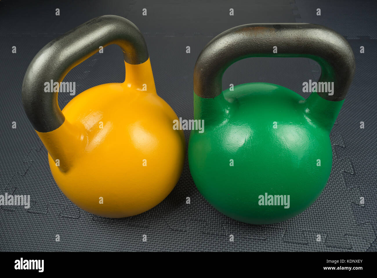 Two competition kettlebells on a fitness studio gym floor. Yellow competition kettlebells weigh 16kg. Green competition - Stock Image