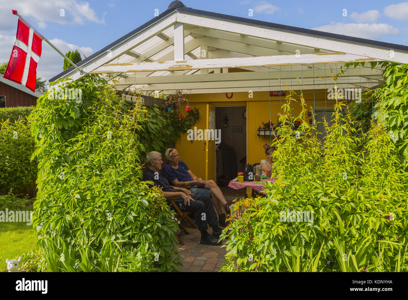 Danish 'cozy' a summer day in the allotment. The flag shows joy and party on a day off with friends.Dansk - Stock Image
