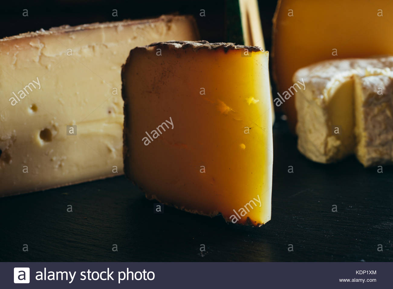 Cheese assortment on black background. Various sorts of cheese for appetizing, gourmet, delicious snacks. Traditional - Stock Image