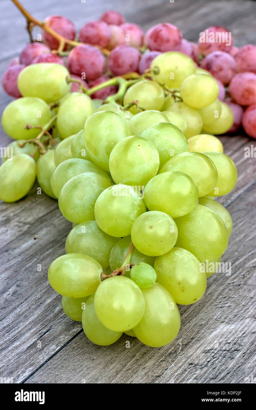 Ripe white and red grapes on a wooden background. - Stock Image