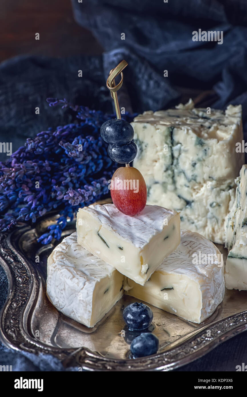Blueberries and grapes with cheese Gorgonzola and Camembert with lavender. Close. Village. The horizontal frame. - Stock Image