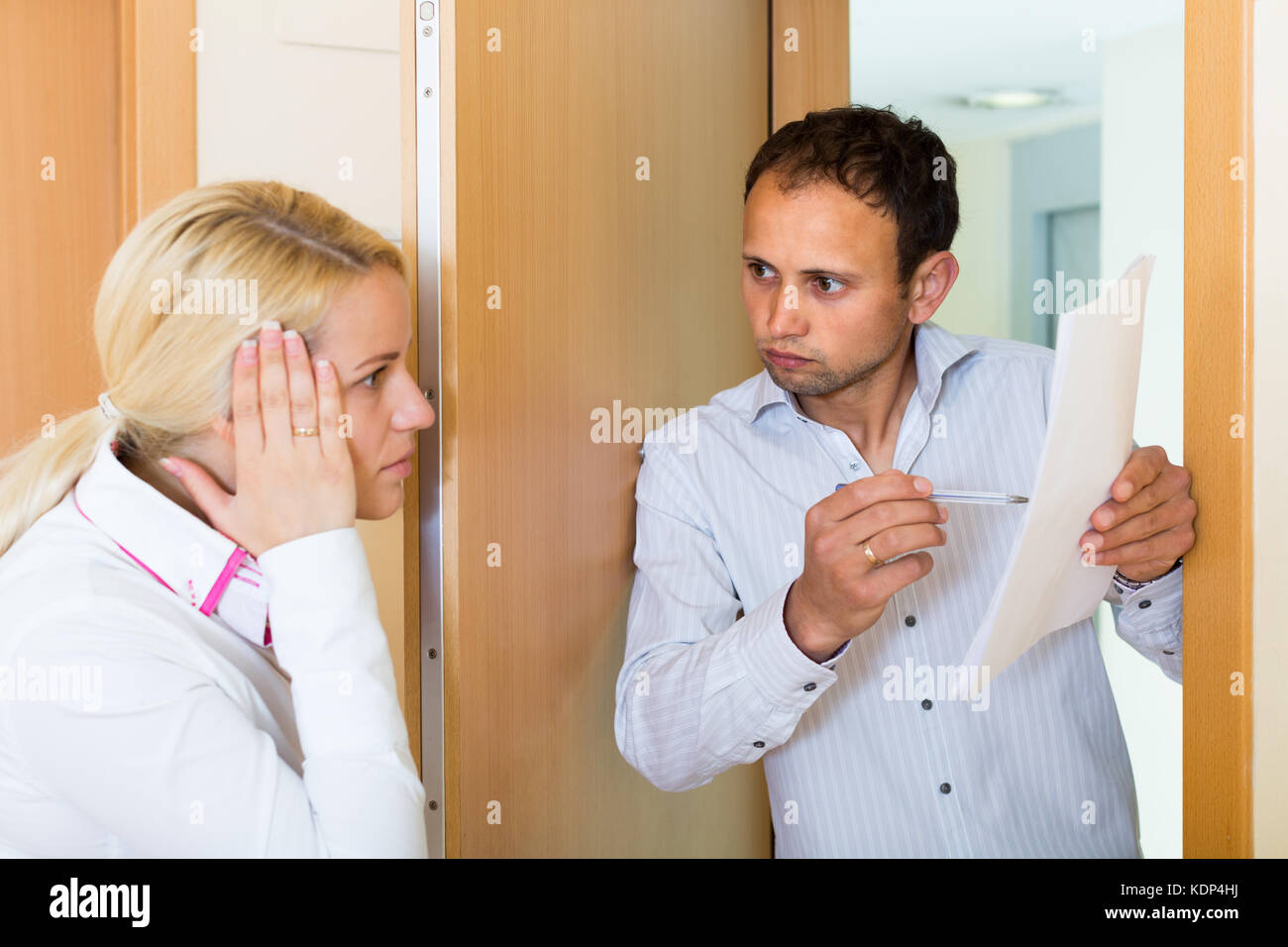 Collector is trying to get the arrears from woman at home door - Stock Image