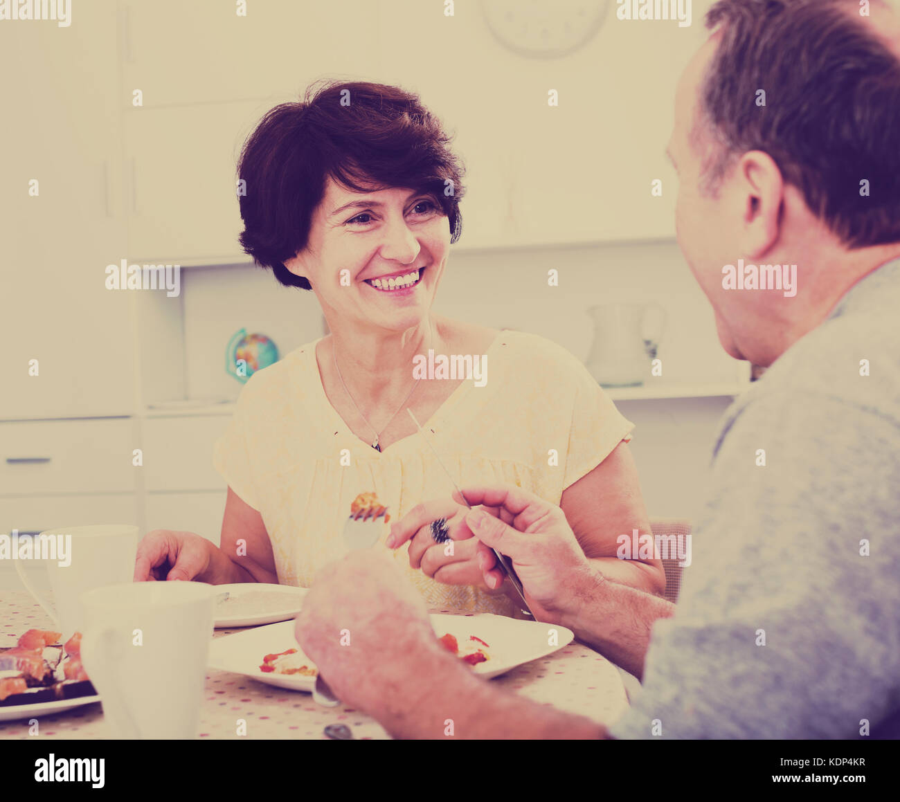 Cheerful mature woman eating lunch and listening to her husband at home Stock Photo