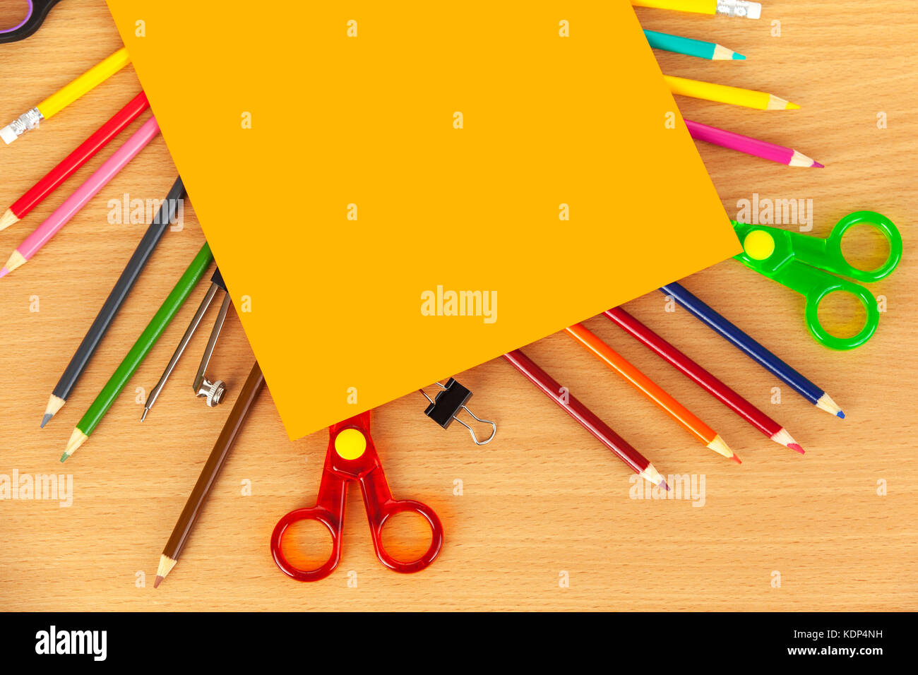 Sheet of orange card laying on top of colouring pencils and safety scissors on a wooden desk Stock Photo