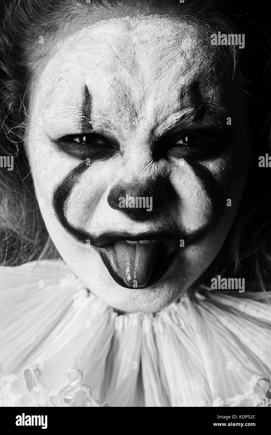angry evil clown, show tongue looking at camera close up, monochrome - Stock Image
