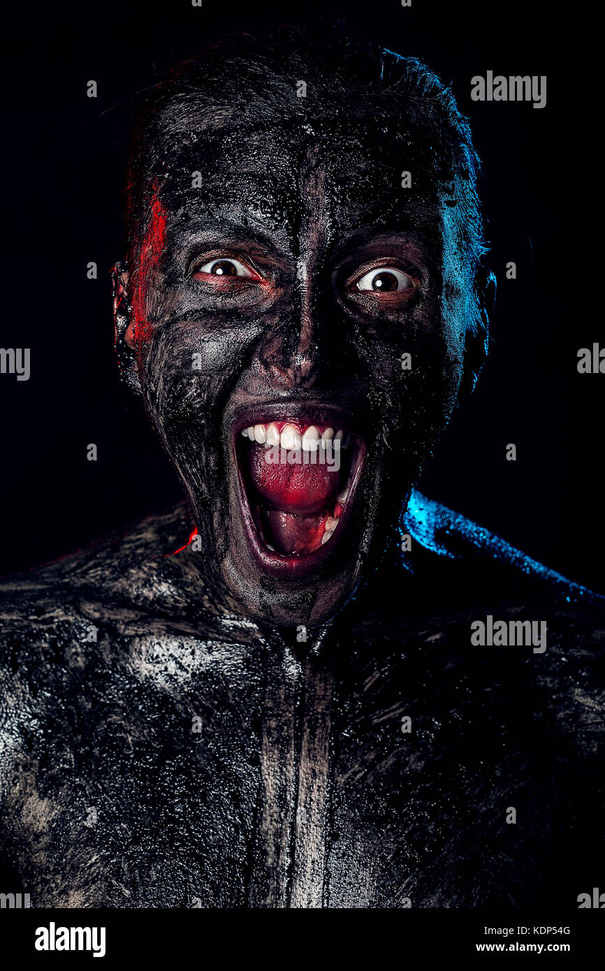 angry dirty zombie attack on black background - Stock Image