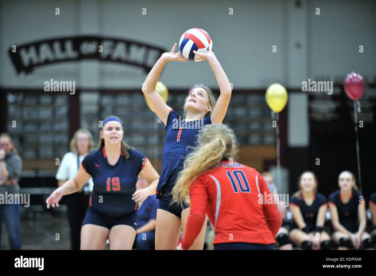 Player setting a shot for a teammate during a high school volleyball match. USA. - Stock Image