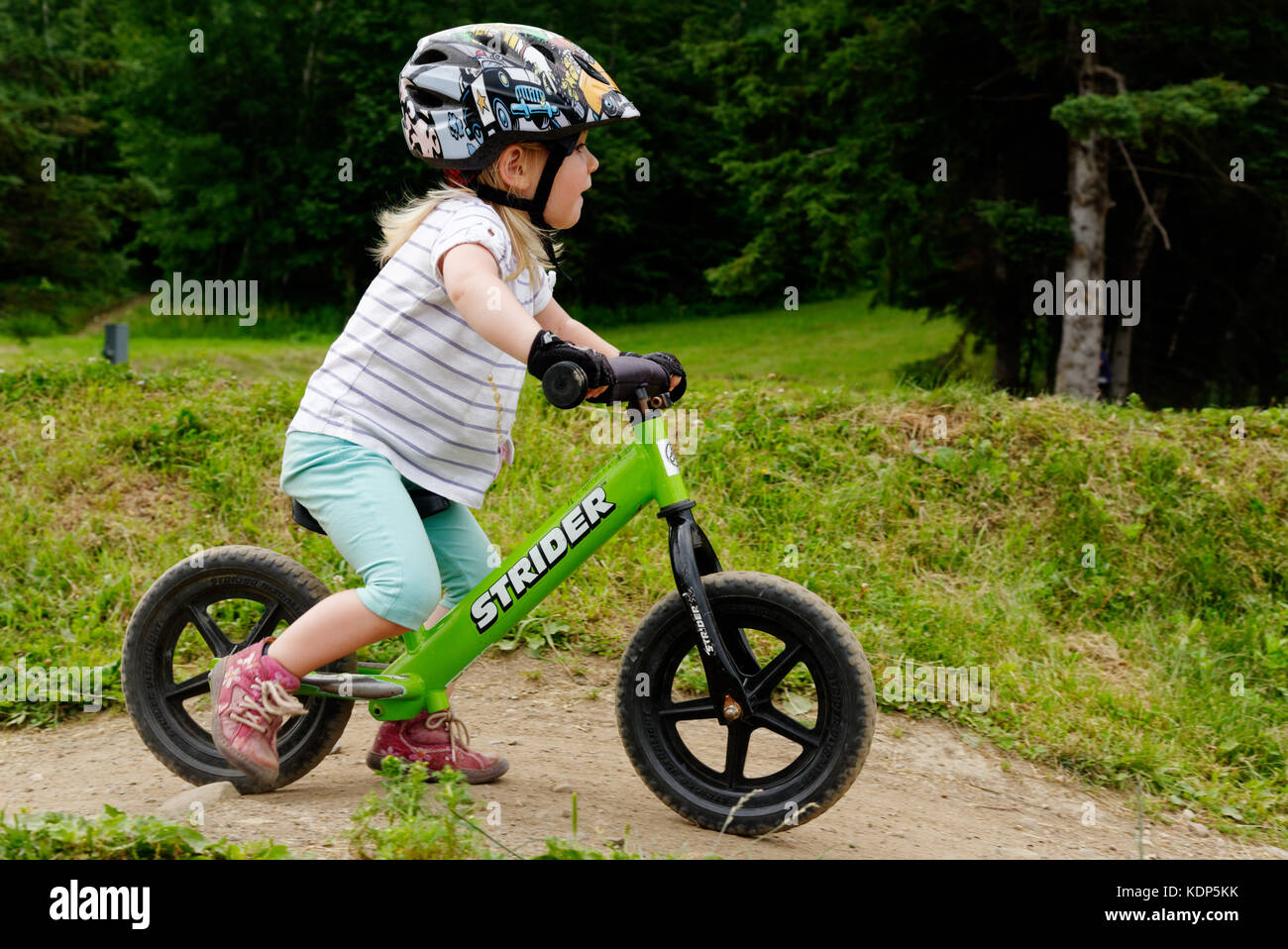 e26e46c803d A three year old girl riding a balance bike - Stock Image
