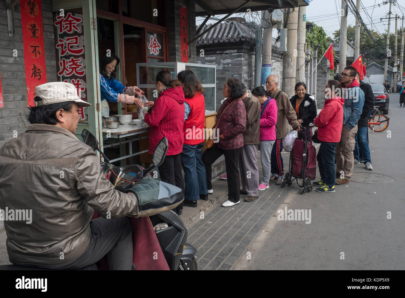 Residents line up to buy cakes in a Hutong in Beijing, China. - Stock Image