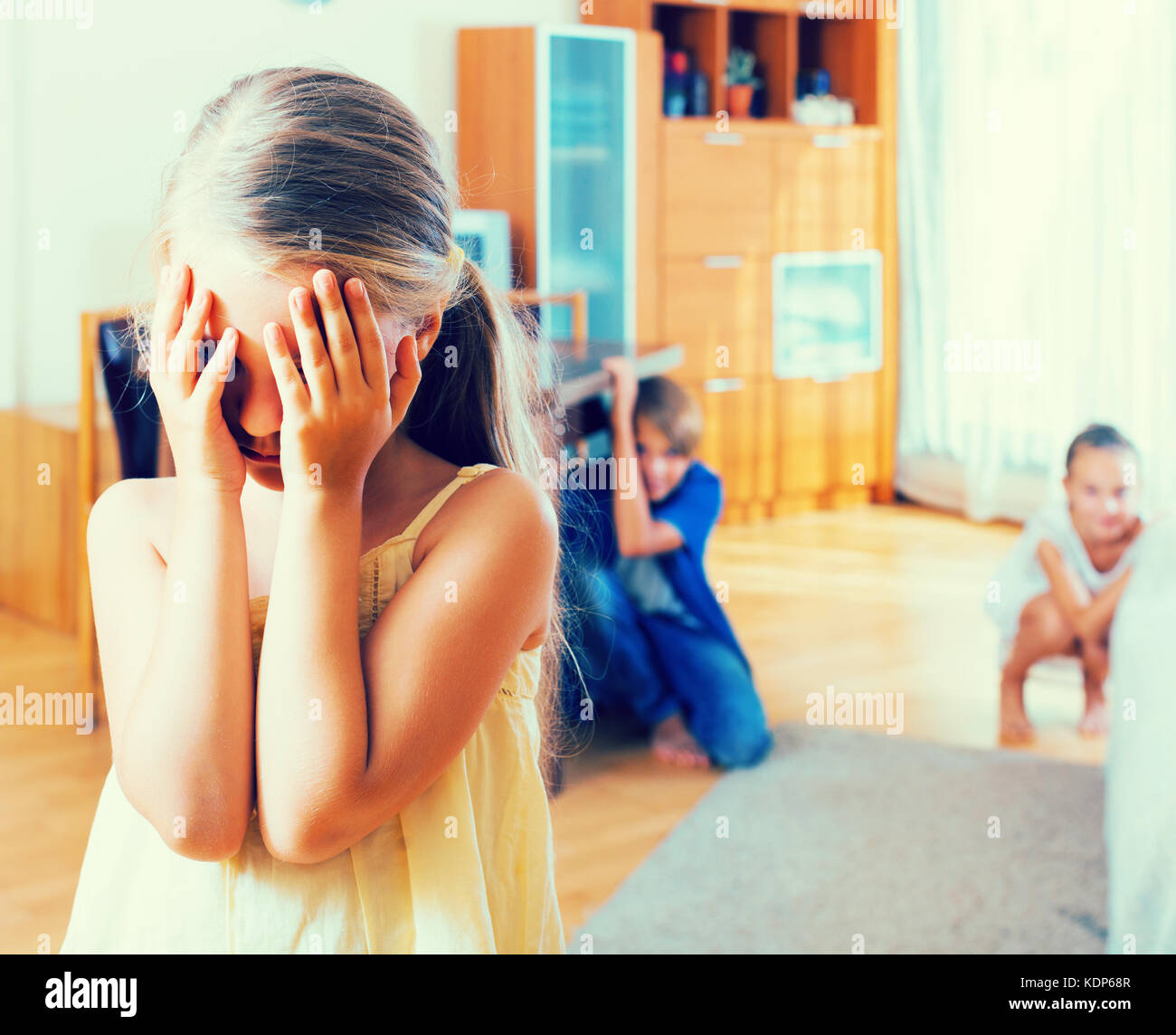Teenage boy with little sisters playing hide-and-go-seek indoors Stock Photo