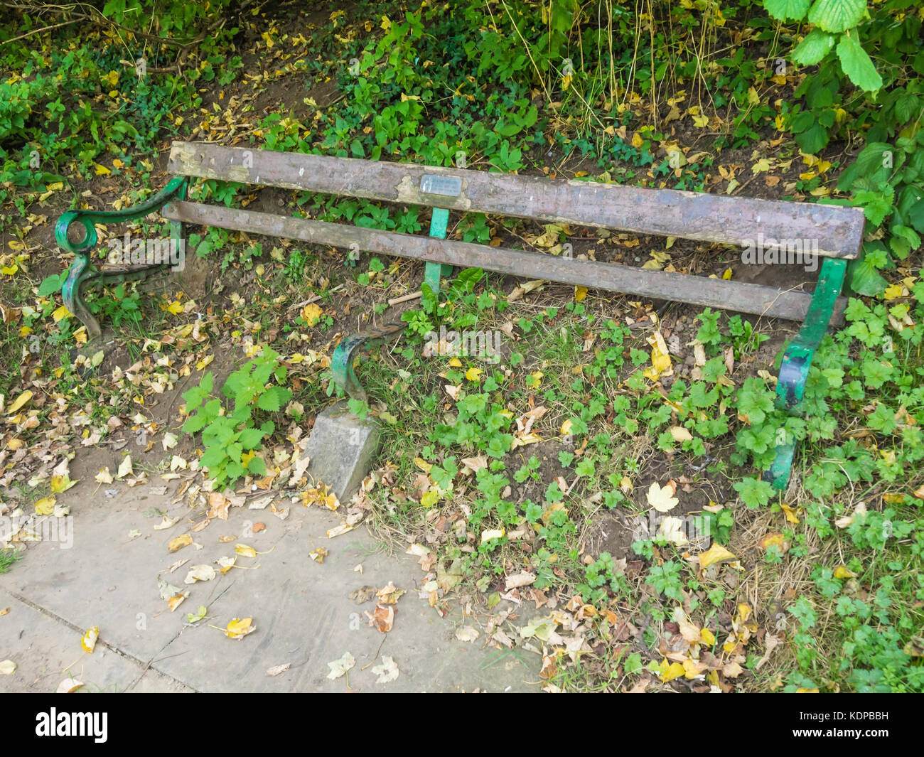 Public bench seat, with a dedication to a couple who died in 1987, with the seat timbers decayed and lost leaving the seat useless Stock Photo