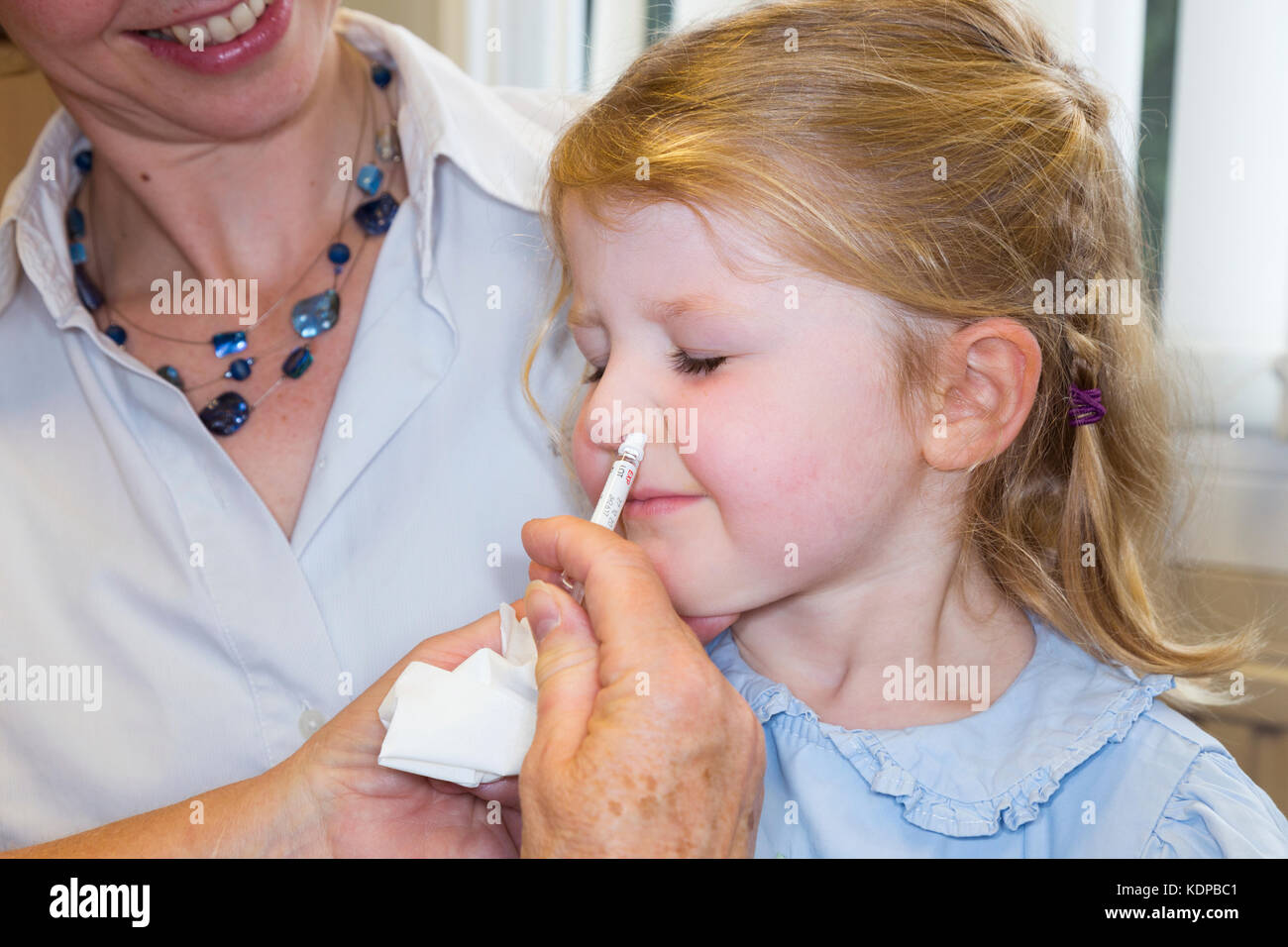 3 year old child, with her mum / mother, receives dose of Fluenz flu vaccine nasal spray immunisation from NHS Practice Stock Photo