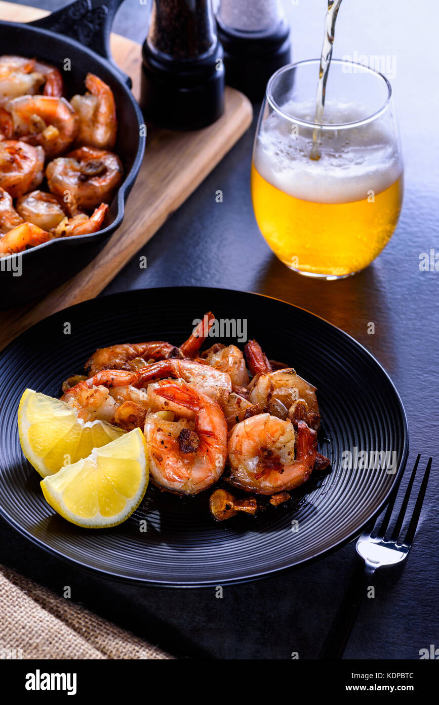 Skillet roasted jumbo shrimp on a black plate. Beer pouring into a glass. - Stock Image