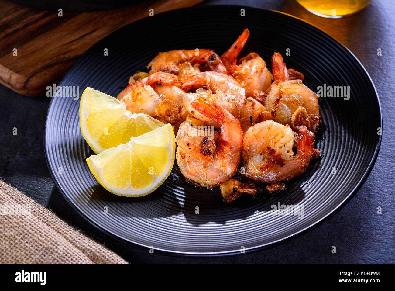 Skillet roasted jumbo shrimp on a black plate. Closeup. Shrimp roasted with sliced garlic and spices. - Stock Image