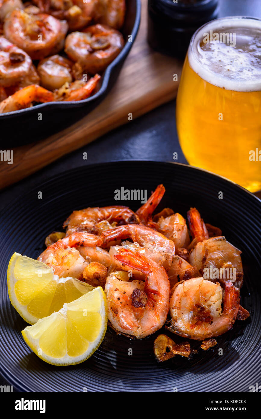 Skillet roasted jumbo shrimp with sliced garlic and spices on a black plate. Closeup. A glass of beer and a skillet - Stock Image