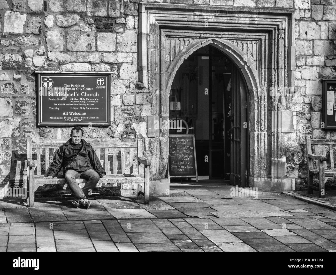 Man sitting by the West Door of St Michael's Church, Southampton, England, UK. - Stock Image