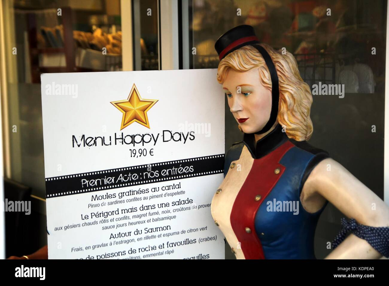 Menu at the French Hollywood themed 'Restaurant Les Jours Heureux, Valras-Plage', with a female mannequin - Stock Image