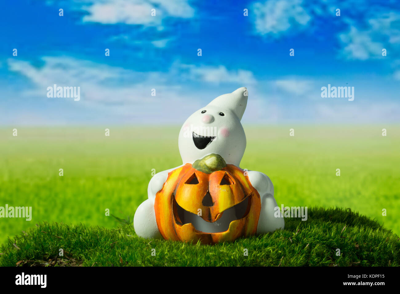 Funny ghost with pumpkin on the green meadow at halloween - Stock Image