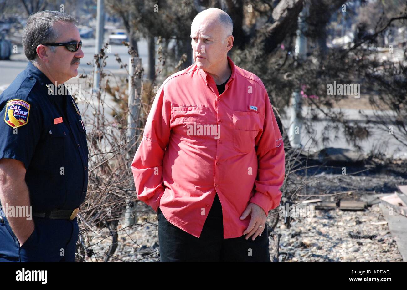 California Gov. Jerry Brown, right, is briefed by CAL FIRE Director Chief Ken Pimlott as they tour the aftermath - Stock Image