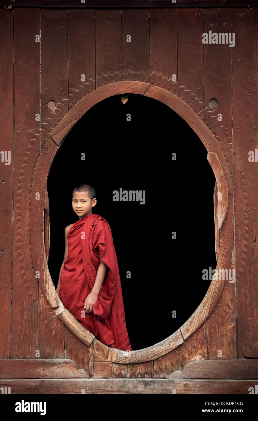 Myanmar, young novice Buddhist monks dressed in robes standing in wooden oval windows at Shwe Yaunghwe Kyaung Monastery - Stock Image