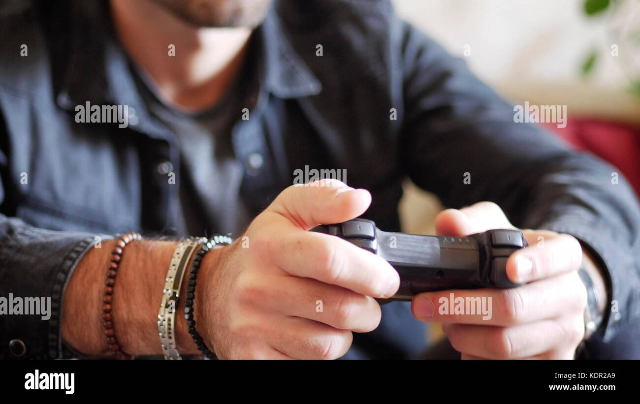 Young man using joystick or joypad for videogames - Stock Image