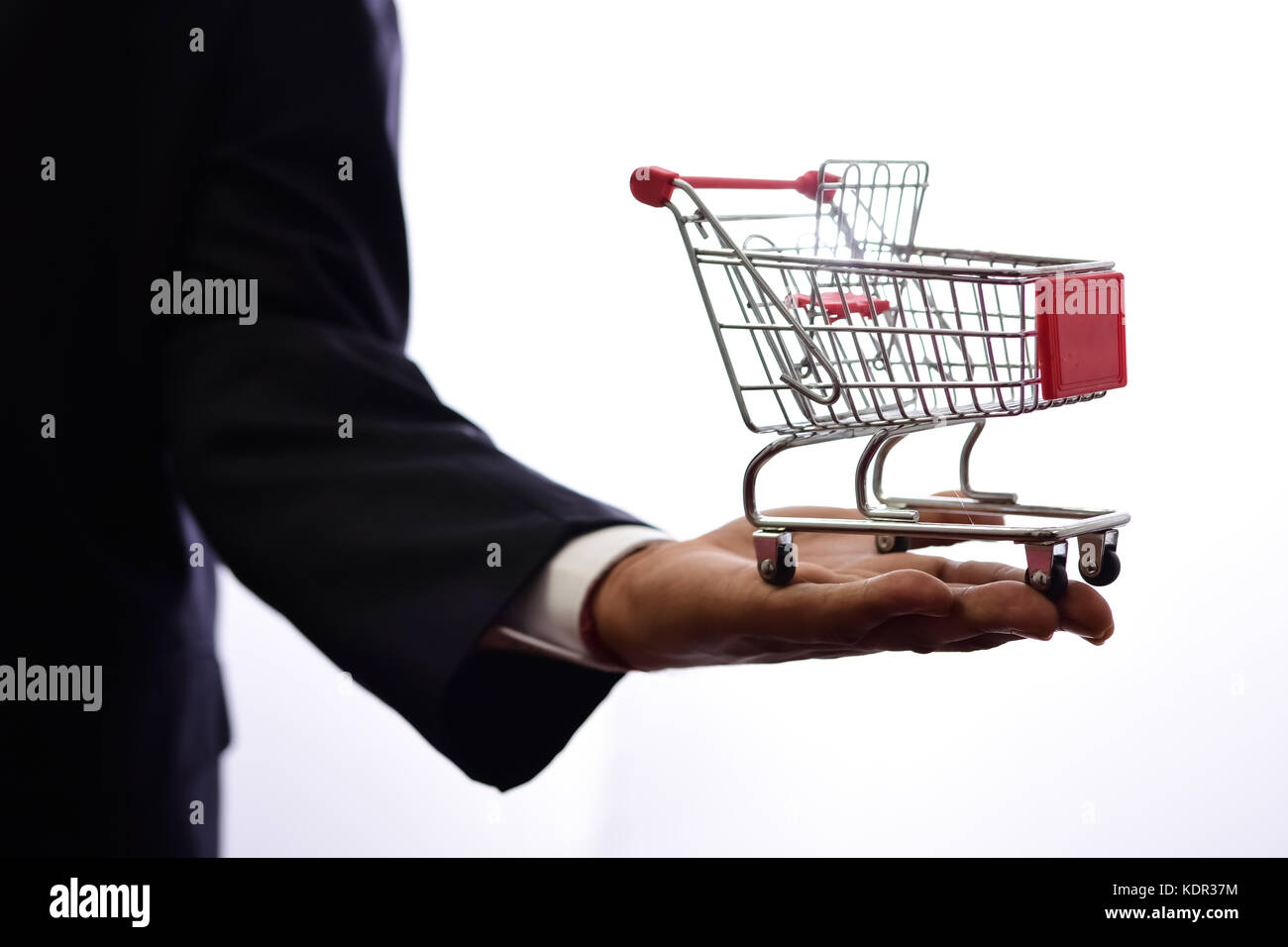 Shopping cart and businessman on white background - Stock Image