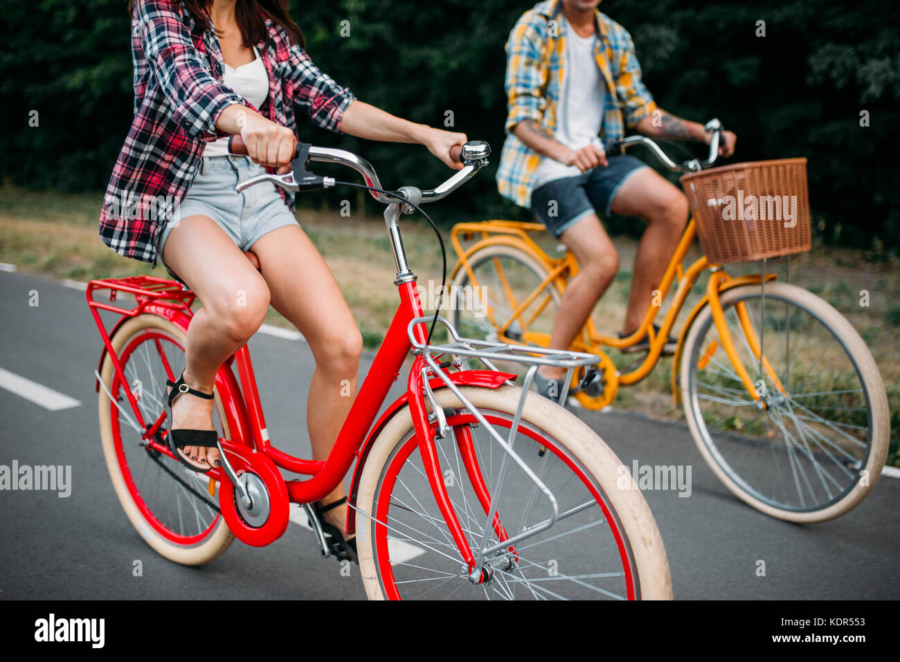 Male and female persons riding on retro bikes  Couple on vintage
