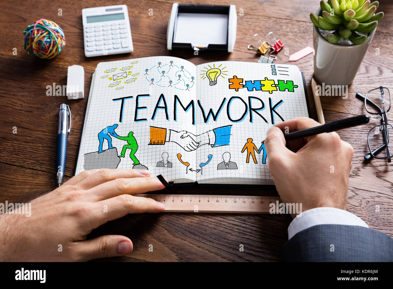 Close-up Of Businessperson Drawing Teamwork Concept On Notebook At Wooden Desk - Stock Image