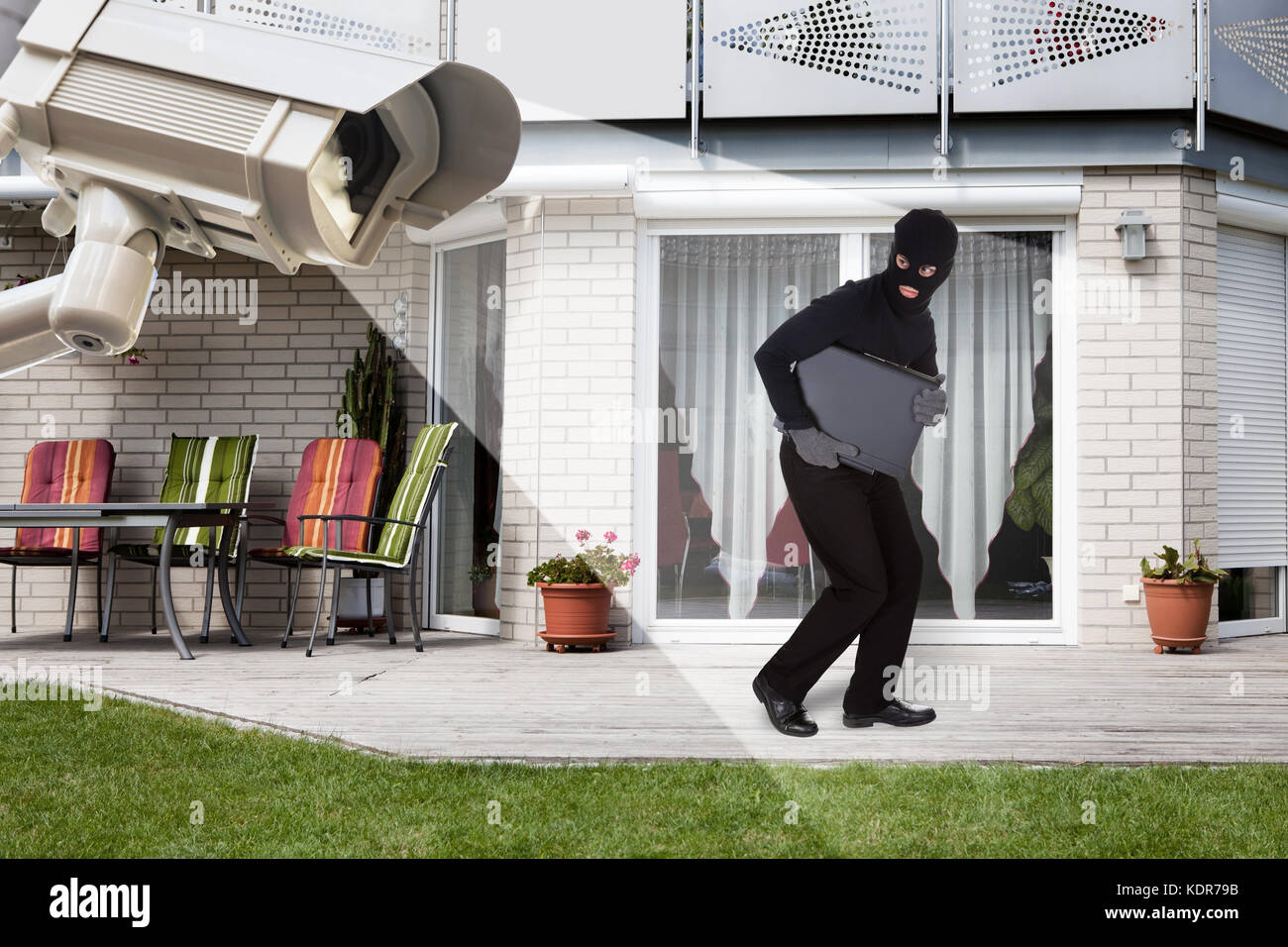 Security Camera Capturing Thief Wearing Balaclava Running With Laptop Outside The House - Stock Image