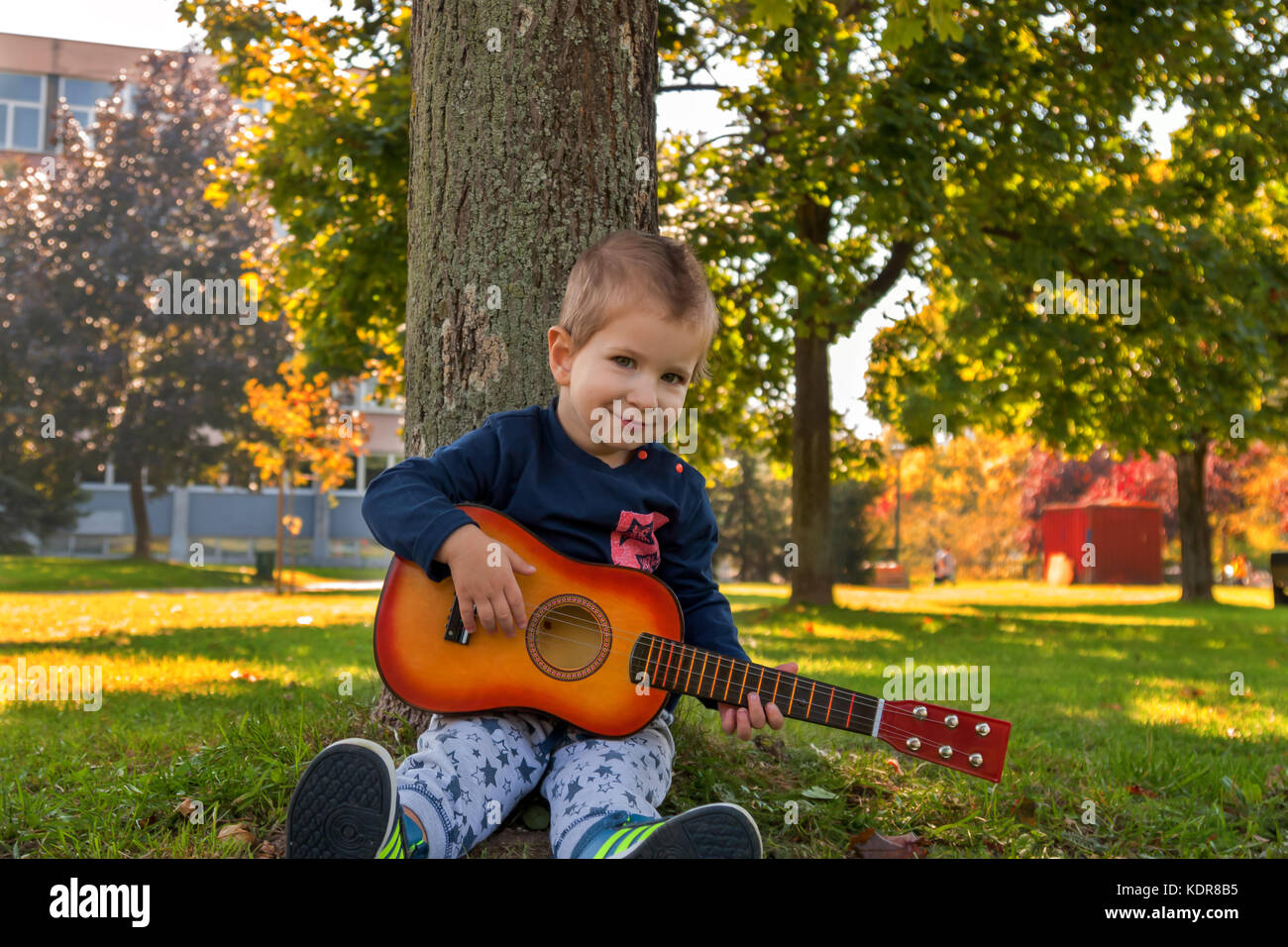 Small boy holding acoustic guitar while sitting leaned on a tree Stock Photo