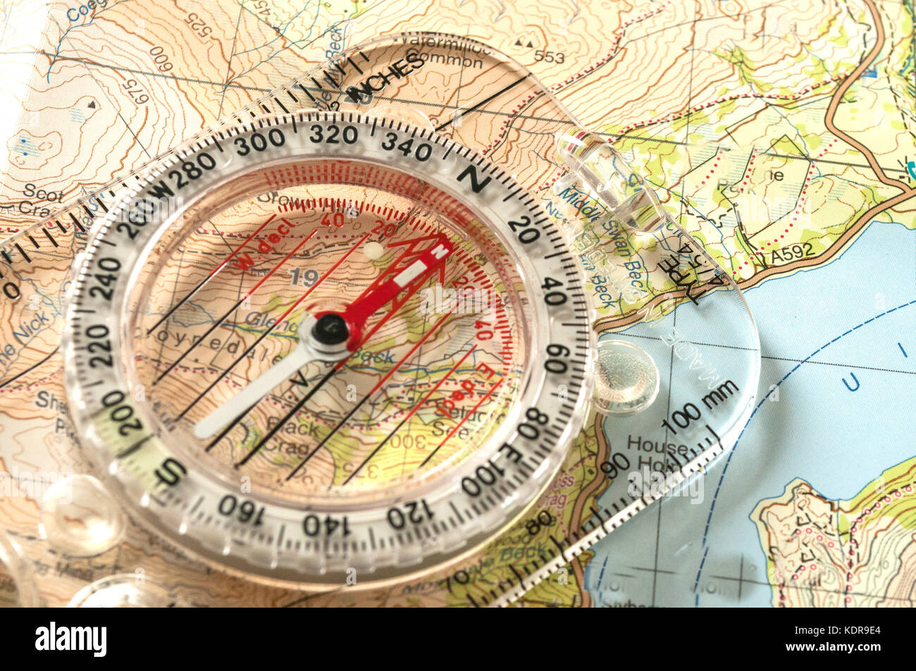 Compass showing direction on Topographic Map, with Rescue Whistle, Shallow Depth of Field - Stock Image